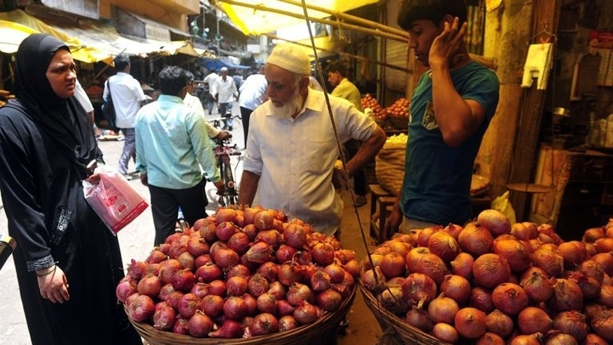 A prospective customer haggles over the price of onions at a market in Mumbai on August 22, 2013.