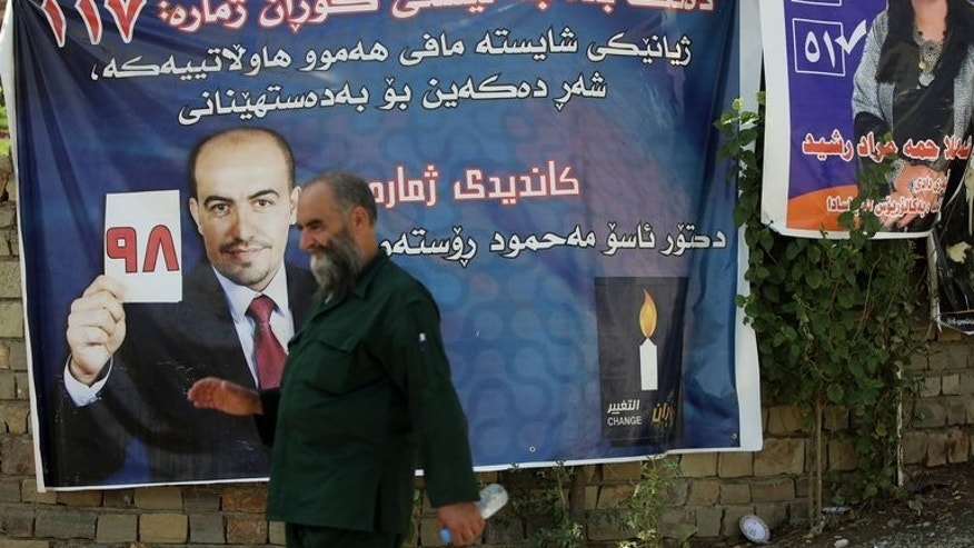 A man walks past a campaign poster of the Movement for Change (MC aka Goran) on September 18, 2013 in Iraq's northern city of Sulaimaniyah ahead of Kurdistan's parliamentary elections