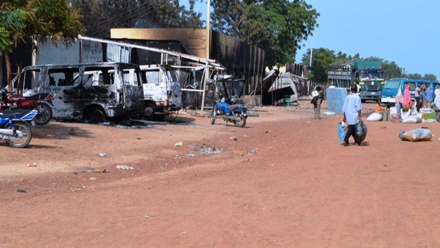 People walk past burnt vehicles and shops in Benisheik on September 19, 2013. Nigeria's military sent reinforcements to the remote northeastern town of Benisheik after Boko Haram Islamists stormed the area, burnt dozens of homes and slaughtered at least 87 people.
