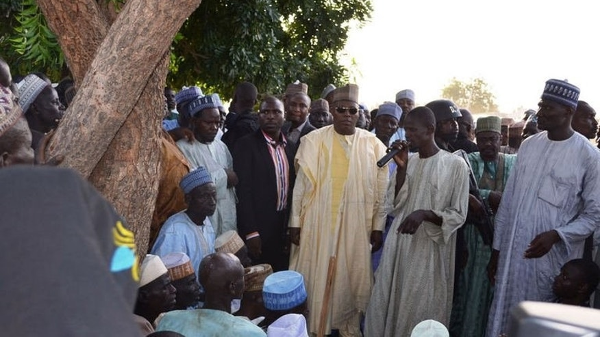A villager speaks next to the governor of Borno State, Kashim Shettima (centre) in Benisheik on September 19, 2013. Nigeria's military sent reinforcements to the remote northeastern town of Benisheik after Boko Haram Islamists stormed the area, burnt dozens of homes and slaughtered at least 87 people.