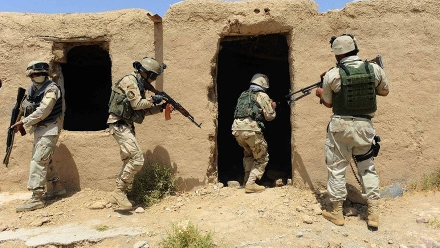 Afghan security forces search a building following an insurgent attack on a road construction workers' camp in Karukh district of Herat on August 17, 2013.