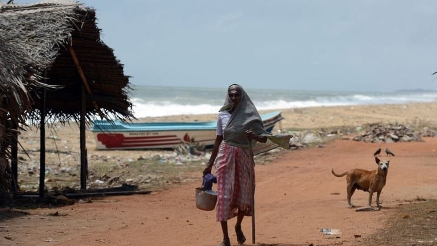 A Sri Lankan woman walks through the village of Udappuwa, from which many people have travelled illegally to Australia.
