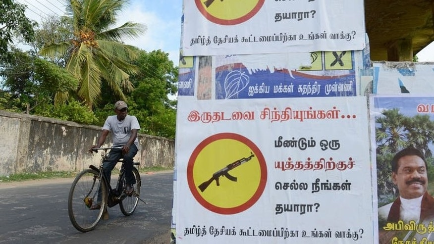 "A Sri Lankan Tamil man cycles past a poster, reading, ""Are you ready to go for another war"" in Jaffna, on September 20, 2013."