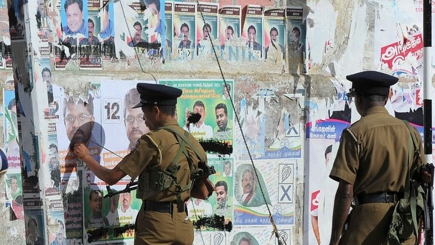 Sri Lankan policemen remove campaign posters of candidates for the Northern Provincial Council election in Jaffna on September 20, 2013.