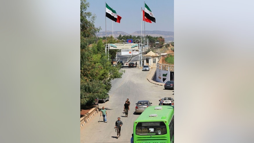 This photo taken on September 16, 2013, shows Free Syria Army (FSA) soldiers running near the Oncupinar border crossing, on the Turkish side of the border, near Kilis.