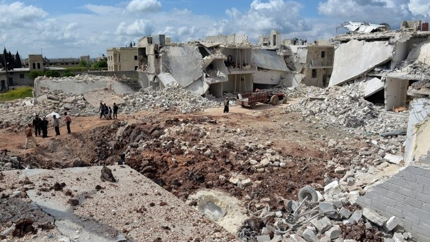 People walk past destroyed houses in the northern Syrian town of Azaz in April. Syria's opposition National Coalition on Friday condemned attacks by Al-Qaeda loyalists of the Islamic State of Iraq and the Levant (ISIS) on mainstream rebels of the Free Syrian Army.