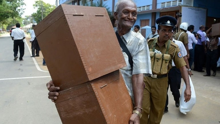 Sri Lankan election workers carry ballot boxes before boarding buses as they prepare to go to their polling centres in Jaffna, 400 kilometres (250 miles) north of the capital Colombo on September 20, 2013.