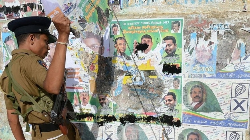 A policeman removes campaign posters of candidates for the Northern Provincial Council election in Jaffna, 400 kilometres (250 miles) north of the capital Colombo on September 20, 2013.