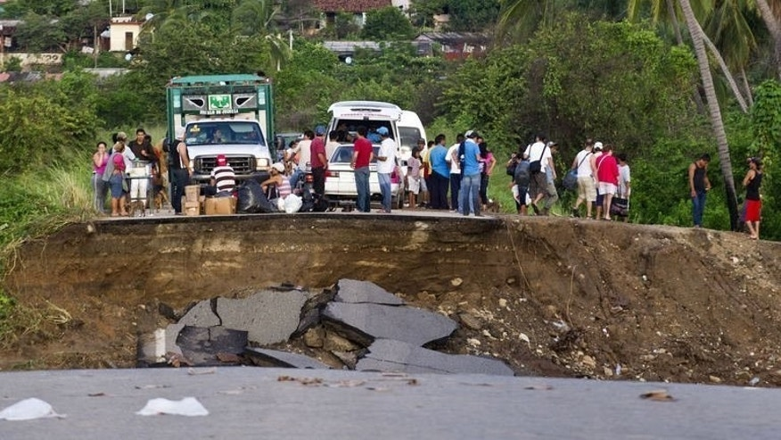 People stand on a destroyed road in Coyuca de Benitez, Guerrero state, on September 21, 2013 as Mexico began the massive task of rebuilding after a rare double onslaught of storms left at least 170 feared dead