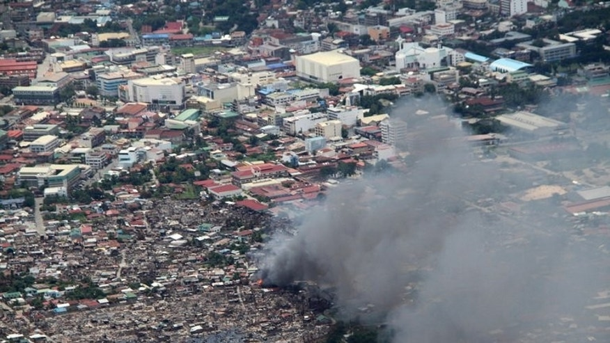 Houses burn during fighting between government forces and Muslim rebels in Zamboanga City, on September 17, 2013.