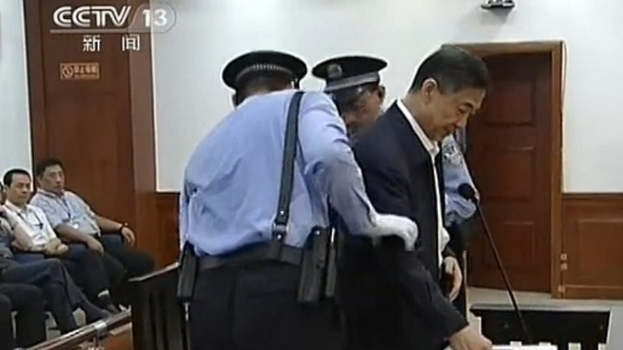 This screen grab taken from state television CCTV footage broadcast on August 25, 2013 shows ousted Chinese political star Bo Xilai (R) being helped to sit in his dock in the courtroom as he stands trial at the Intermediate People's Court in Jinan, in eastern China's Shandong province.