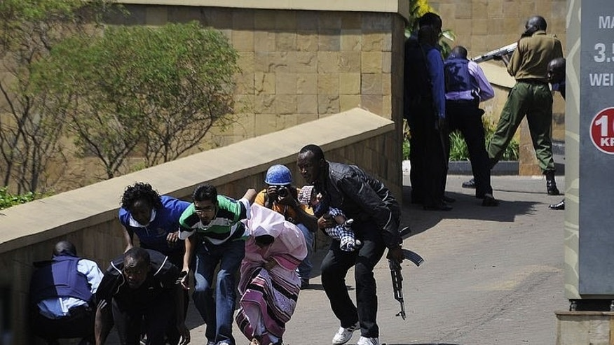 A policeman carries a baby to safety after masked gunmen stormed an upmarket mall and sprayed gunfire on shoppers and staff on September 21, 2013 in Nairobi.