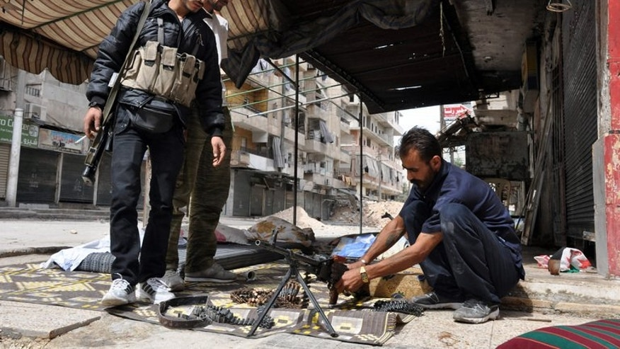 A rebel fighter cleans his weapon as two of his comrades look on in the northern Syrian city of Aleppo on September 20, 2013.