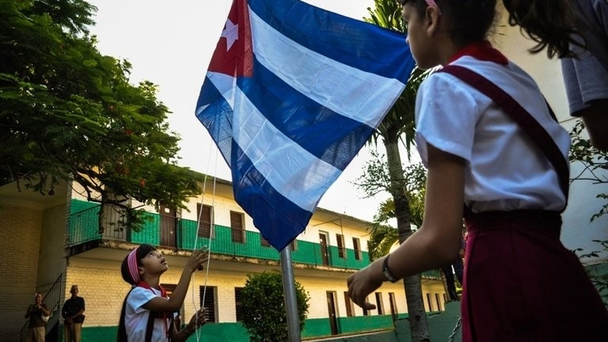 Schoolgirls raise the Cuban national flag, Havana, September 2, 2013. Cuba and the United States have reached a rare preliminary agreement on working together more closely, in the field of air and maritime rescue, Havana's state newspaper Granma said.