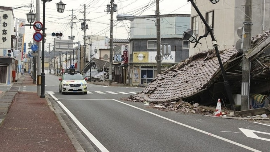 "A Google car mounted with a street view camera drives through a street in Namie, on March 28, 2013. namie -- a town abandoned after the Fukushima nuclear accident -- has protested Prime Minister Shinzo Abe's global promise that the situation of the crippled plant was ""under control""."