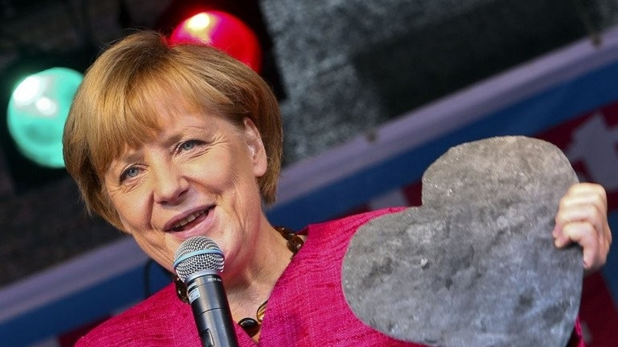 German Chancellor Angela Merkel holds a heart-shaped piece of slate during an election campaign event on September 21, 2013.