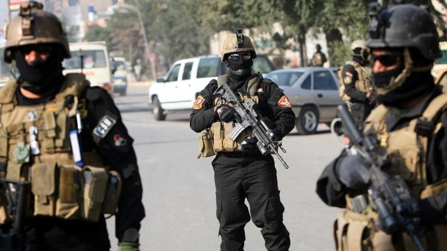 Iraqi anti-terror police stand guard at a checkpoint in Baghdad, on January 6, 2011. At least four police officers have been killed after suicide bombers attacked their base in Baiji, according to a fellow officer and a doctor.