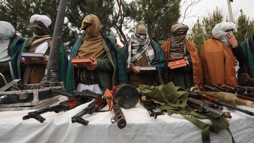 Taliban fighters stand with their weapons in Herat, Afghanistan, on February 18, 2012.