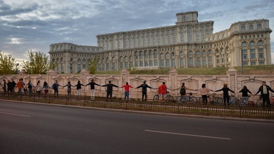 Thousands of Romanians form a human chain around parliament in Bucharest on September 21, 2013 to protest a Canadian company's plan to open Europe's largest gold mine in a picturesque Transylvanian village.