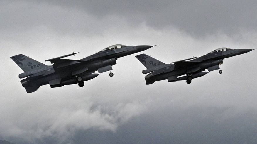 "Two F-16 fighters take-off from the Hualien air force base in eastern Taiwan, on January 23, 2013. Taiwan's air force will be armed with ""smart"" munitions before the year's end that could be used against any Chinese invasion by striking airfields and harbours on the mainland, according to a report in the China Times."