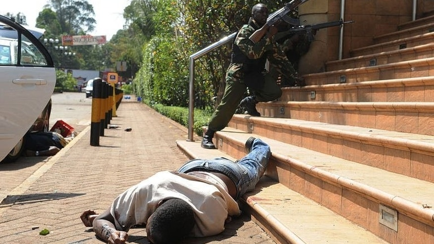 The body of a man lies on the ground as armed policemen try to get entry after masked gunmen stormed an upmarket mall and sprayed gunfire on shoppers and staff, killing at least six on September 21, 2013 in Nairobi.