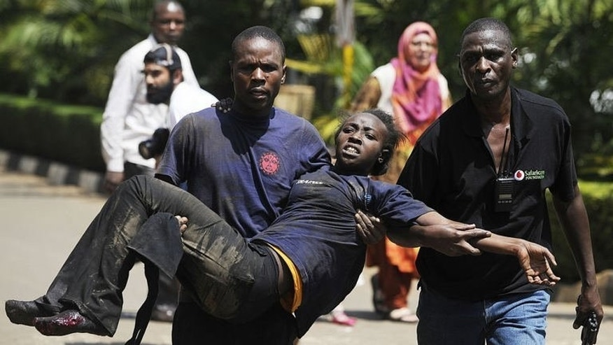 A Kenyan woman is helped to safety after masked gunmen stormed an upmarket mall and sprayed gunfire on shoppers and staff on September 21, 2013 in Nairobi