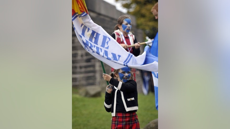"A child with her face painted with the Scottish flag looks on as pro-independence supporters gather for a rally in Edinburgh on September 21, 2013. Voting for Scottish independence is ""common sense"", the leader of the movement to break away from the United Kingdom insisted a year to the day befor Scotland votes in a referendum."