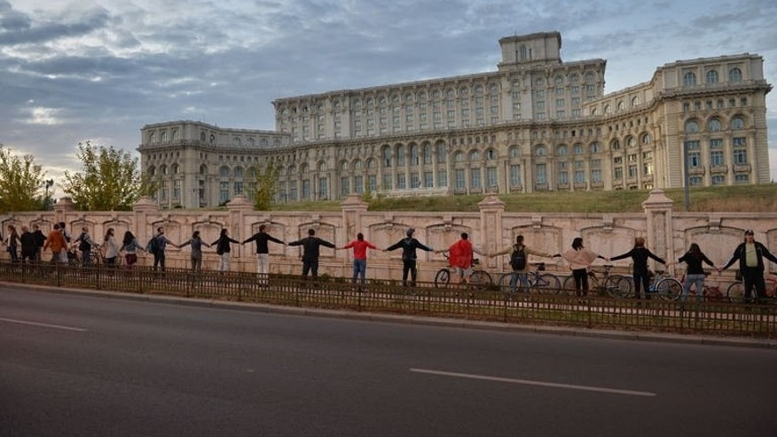 People stand together to form a human chain around the Romanian Parliament building in a protest against the Rosia Montana Gold Corporation (RMGC), a Canadian gold mine project using cyanide, in Bucharest on September 21, 2013.