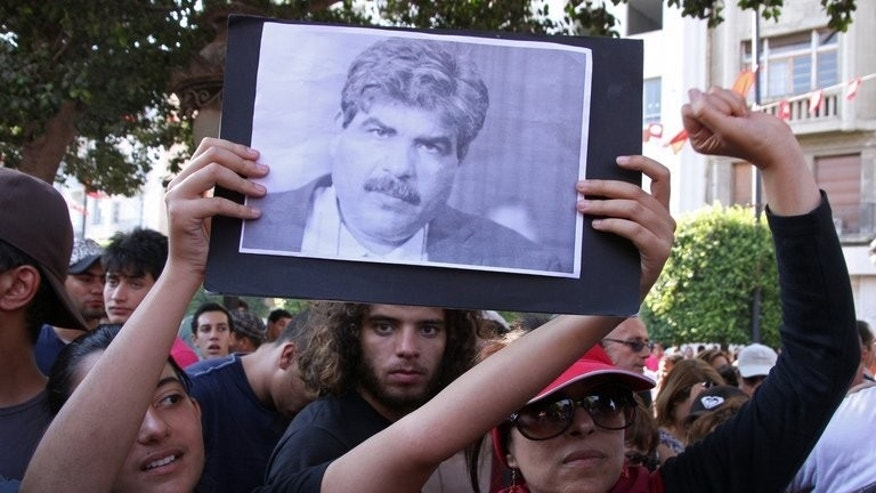 Tunisians shout slogans in front of the interior ministry headquarters following the assassination of leading opposition figure Mohamed Brahmi (portrait) on July 25, 2013 in Tunis.