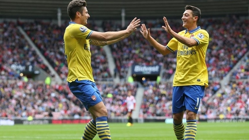 Arsenal's Mesut Ozil (R) congratulates striker Olivier Giroud after Giroud scored their first goal during an English Premier League match against Sunderland at the Stadium of Light in Sunderland, on September 14, 2013.