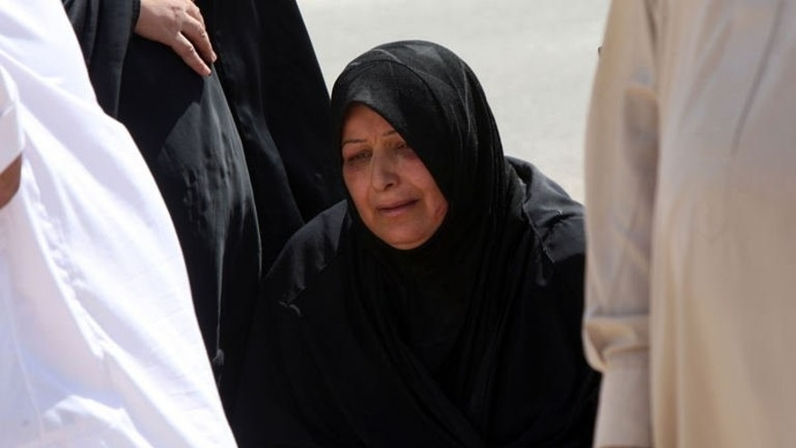 The mother of late Ali Adnan, 23-years old, mourns as they bury her son at a cemetery in the city of Najaf on September 22, 2013, who was killed when two bombs detonated near a funeral tent in the Sadr City district of Baghdad the previous day.