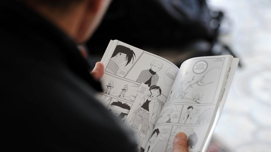"A man reads ""The Revolution"" on September 18, 2013 in Algiers, a manga comic book created by Algerian artist, Fella Matougui, for the 50th anniversary of Algeria's independence."