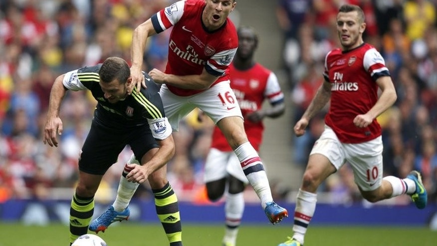 Arsenal's Aaron Ramsey (second left) and Stoke City's Erik Pieters at the Emirates Stadium, London on September 22, 2013. Arsenal went to the top of the English Premier League table after a 3-1 victory at home to Stoke on Sunday.