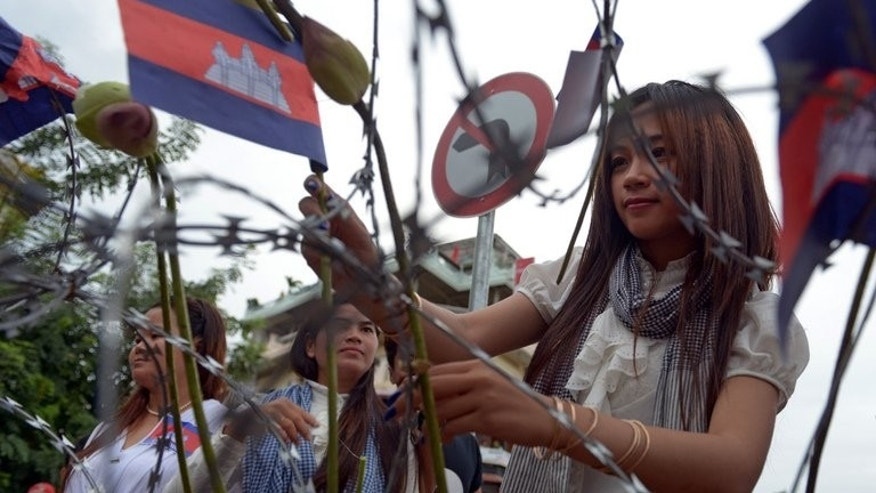 Supporters of the opposition Cambodia National Rescue Party (CNRP) lay flowers and national flags on barbed wire during a protest near the Royal Palace in Phnom Penh on September 21, 2013. Cambodia's parliament convened despite a boycott by the opposition, as the country is gripped by political crisis following disputed elections that led to mass protests and violence.
