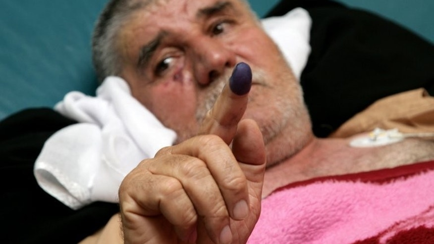 An Iraqi Kurdish man shows his ink-strained finger after casting his ballot from an hopsital bed on September 21, 2013.