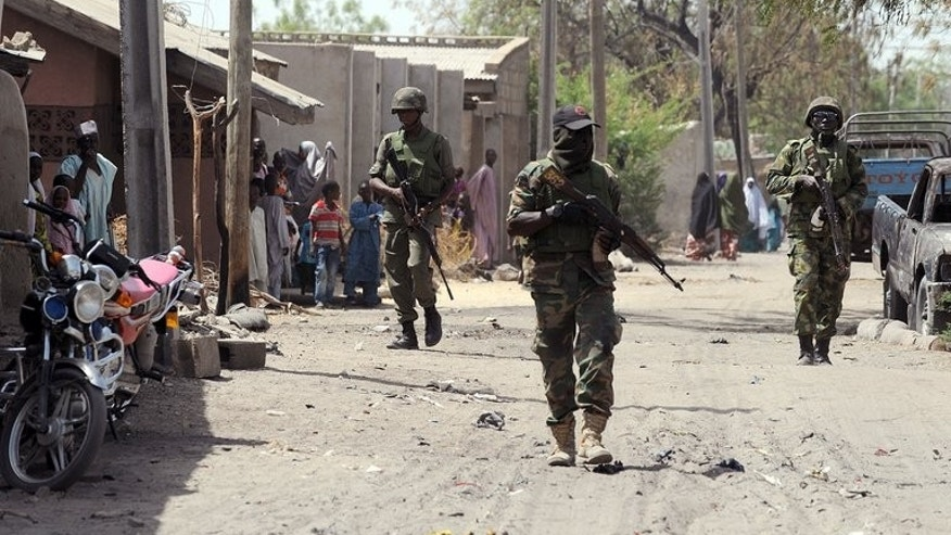 Nigerian troops patrolling in the streets of the remote northeast town of Baga, Borno State on April 30, 2013. The death toll from an attack in northeastern Nigeria that saw insurgents dressed as soldiers set up checkpoints and gun down travellers on a highway has risen to at least 142, an official said Sunday.