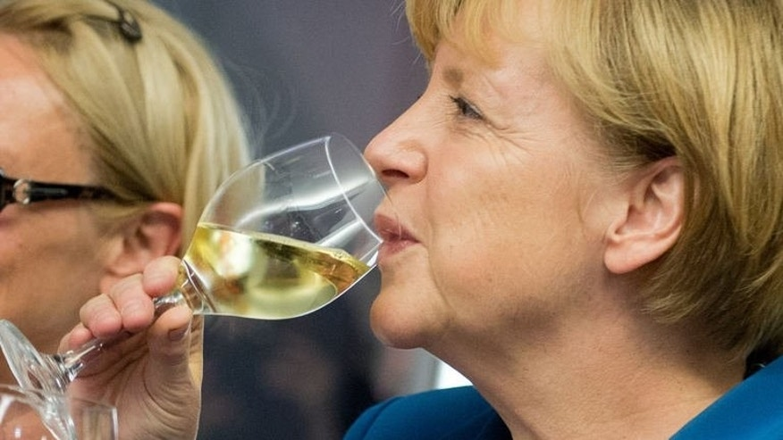 German Chancellor Angela Merkel drinks a glass of wine during the election party of her Christian Democratic Union (CDU) party at the party's headquarters in Berlin on September 22, 2013.
