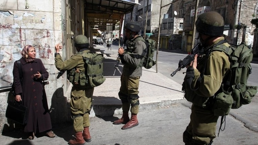 Israeli soldiers stop a Palestinian woman in the Palestinian side of the city of Hebron, on March 27, 2013.