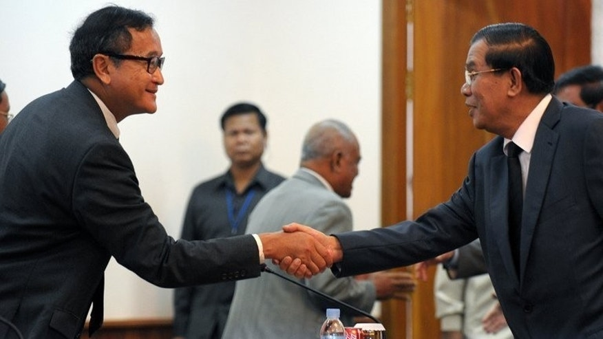 Cambodian Prime Minister Hun Sen (right) shakes hands with opposition leader Sam Rainsy during a meeting at the National Assembly in Phnom Penh, on September 17, 2013. Despite mass protests, accusations of rigged elections, a brief hunger strike by a prince and a threatened boycott of parliament by his rivals, Cambodia's long-ruling strongman Hun Sen remains firmly in control.