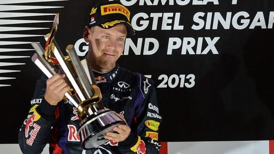 Red Bull driver Sebastian Vettel of Germany holds the trophy on the podium after winning the Formula One Singapore Grand Prix on September 22, 2013.