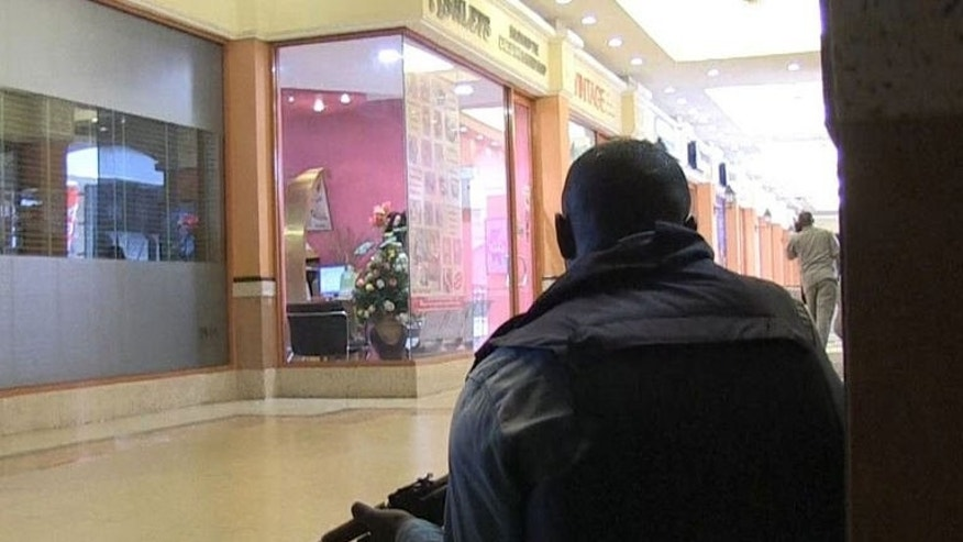 An image grab taken from AFP TV shows a member of the Kenyan security forces taking position inside a shopping mall following an attack by masked gunmen in Nairobi on September 21, 2013.