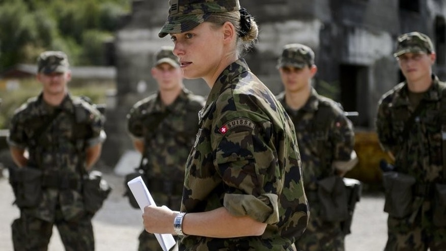 A Swiss army captain stands with prospective officers on September 19, 2013, in Epeisse near Geneva.