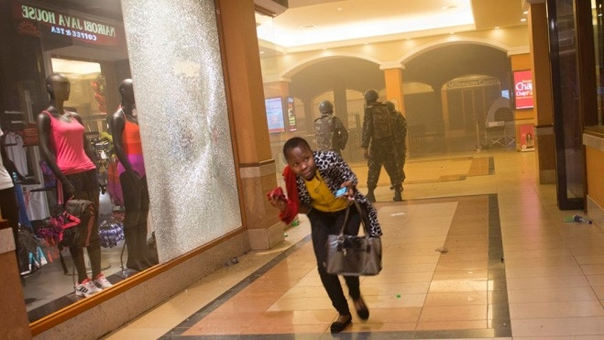 Sept. 21, 2013: A woman who had been hiding during the gun battle runs for cover after armed police, seen behind, enter the Westgate Mall in Nairobi, Kenya.