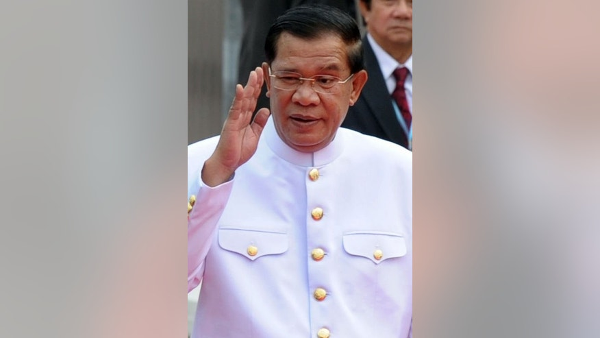 Cambodia's Prime Minister Hun Sen greets people during the first parliament meeting at the National Assembly building in Phnom Penh on September 23, 2013.
