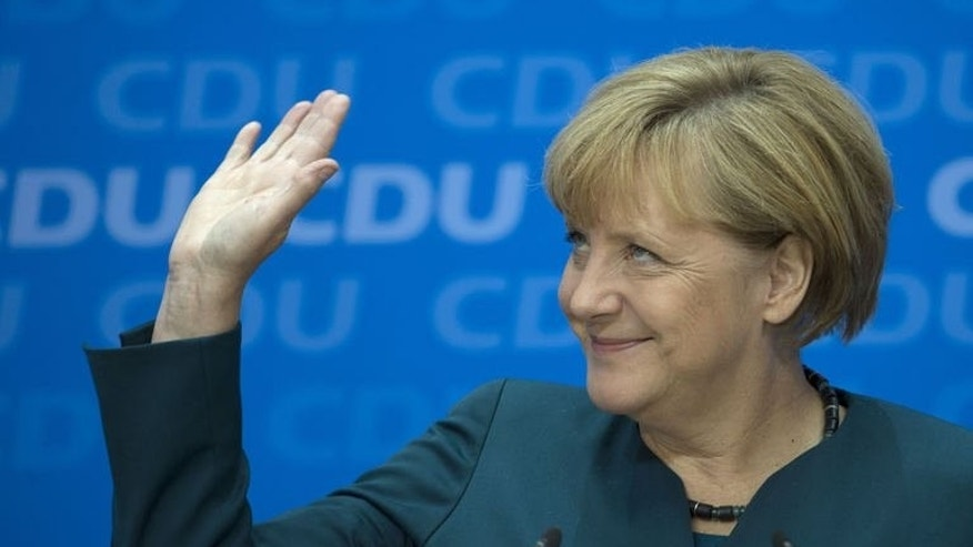 German Chancellor Angela Merkel waves as she gives a press conference in Berlin, on September 23, 2013, a day after the German general elections.