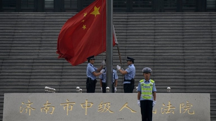 Police raise the Chinese flag outside the Intermediate People's Court in Jinan, Shandong Province on September 22, 2013.
