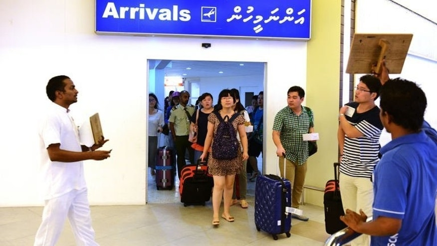 Hotel guides wait for Chinese tourists as they walk out of the international arrivals hall at the Male International Airport on September 5, 2013. The travellers pouring off flight LV199 from Shanghai into the international airport of the Maldives, many dressed in designer labels, are an unmissable sign of China's interest in the far-flung archipelago.