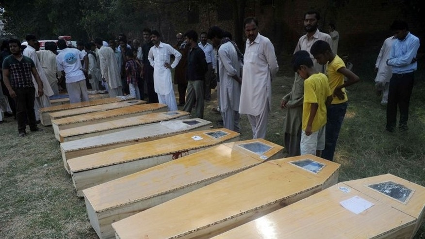 Christians mourn beside the coffins of relatives killed in suicide bomb attacks on a Peshawar church on September 22, 2013.