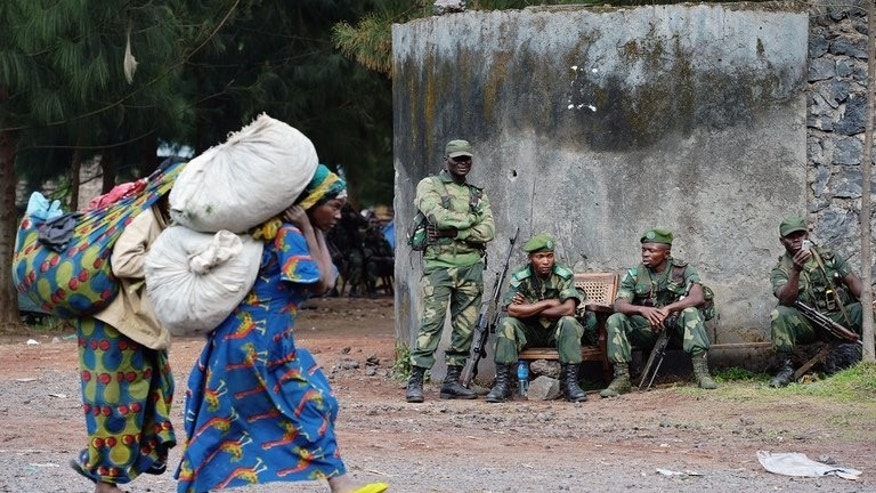 Congolese women walk past Democratic Republic of Congo soldiers near Kibati, near Goma on September 4, 2013. African leaders have called on the DR Congo government and rebels to quickly make an accord to end renewed conflict.