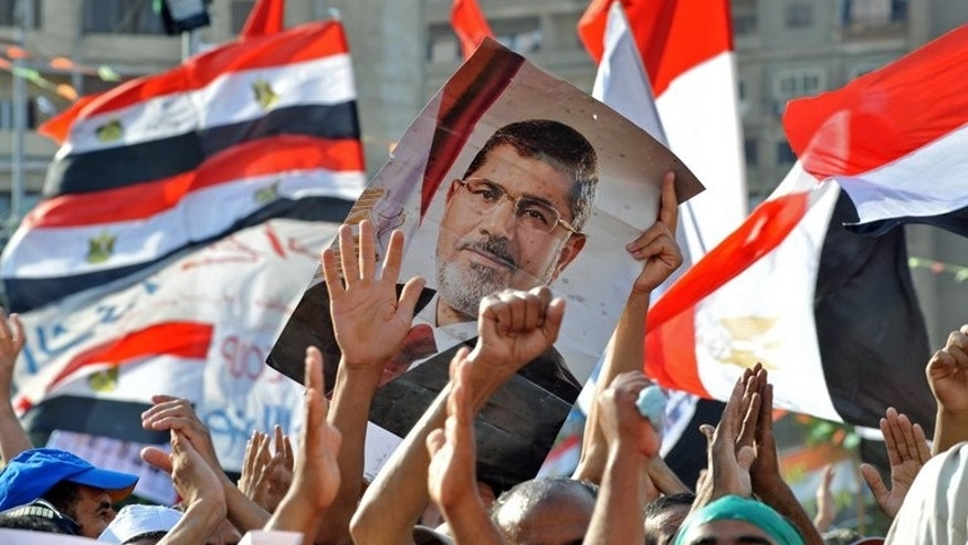 Muslim Brotherhood supporters hold a portrait of Mohamed Morsi during a rally outside the Rabaa al-Adawiya mosque in Cairo, on July 24, 2013. An Egyptian court has banned the Muslim Brotherhood from operating and ordered its assets seized, in the latest blow to the Islamist movement of Morsi.
